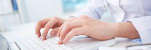 hands typing at white laptop keyboard